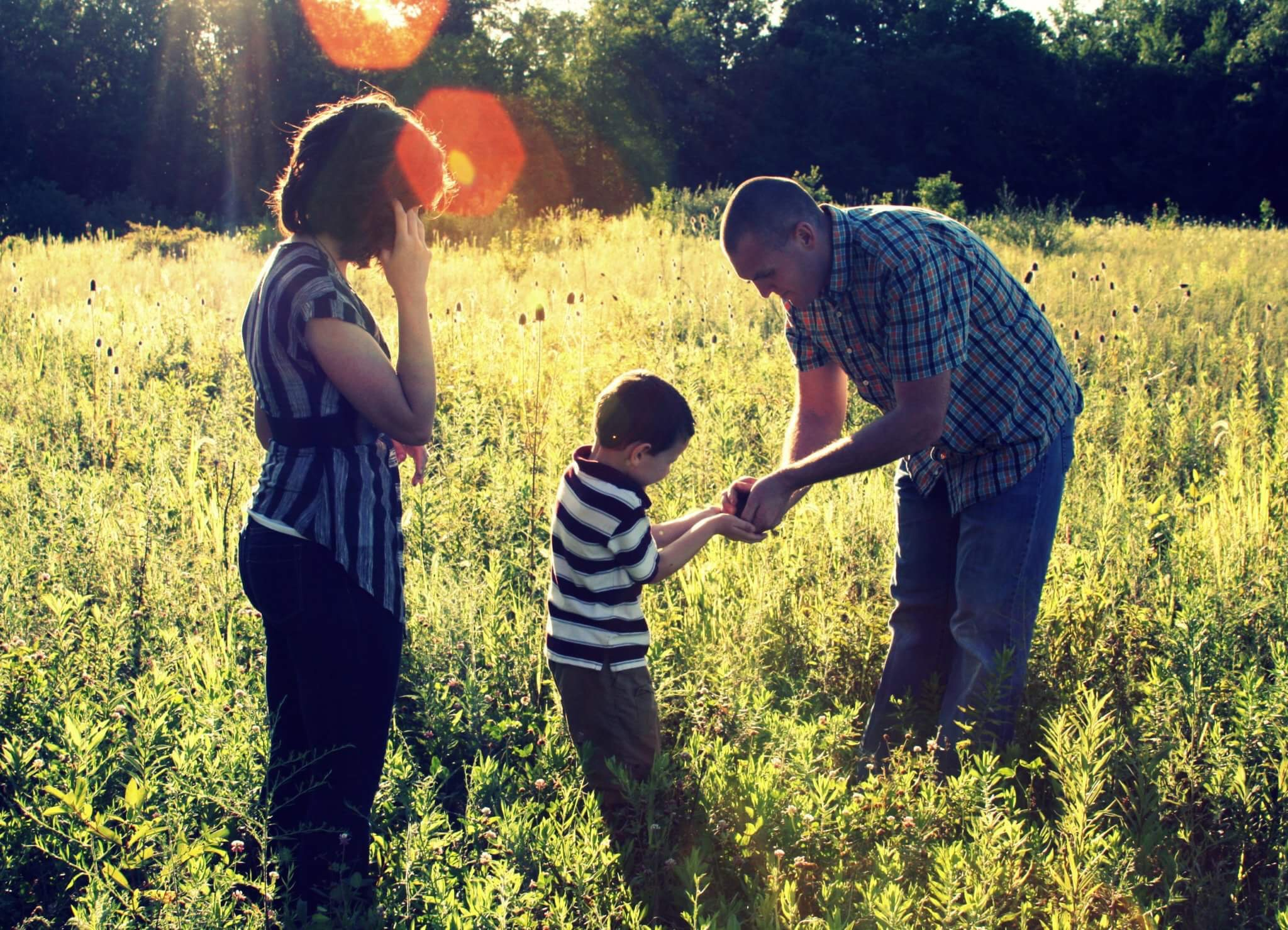 mother, father, and son in a field of grass